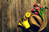 Gardening tools, flowers, watering can and straw hat