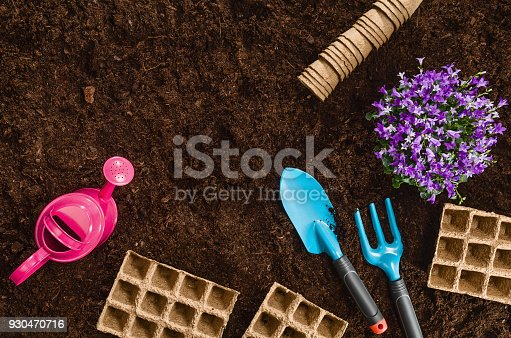 927125180 istock photo Gardening tools on garden soil texture background top view 930470716