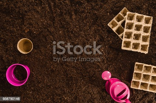 927125180 istock photo Gardening tools on garden soil texture background top view 938790146