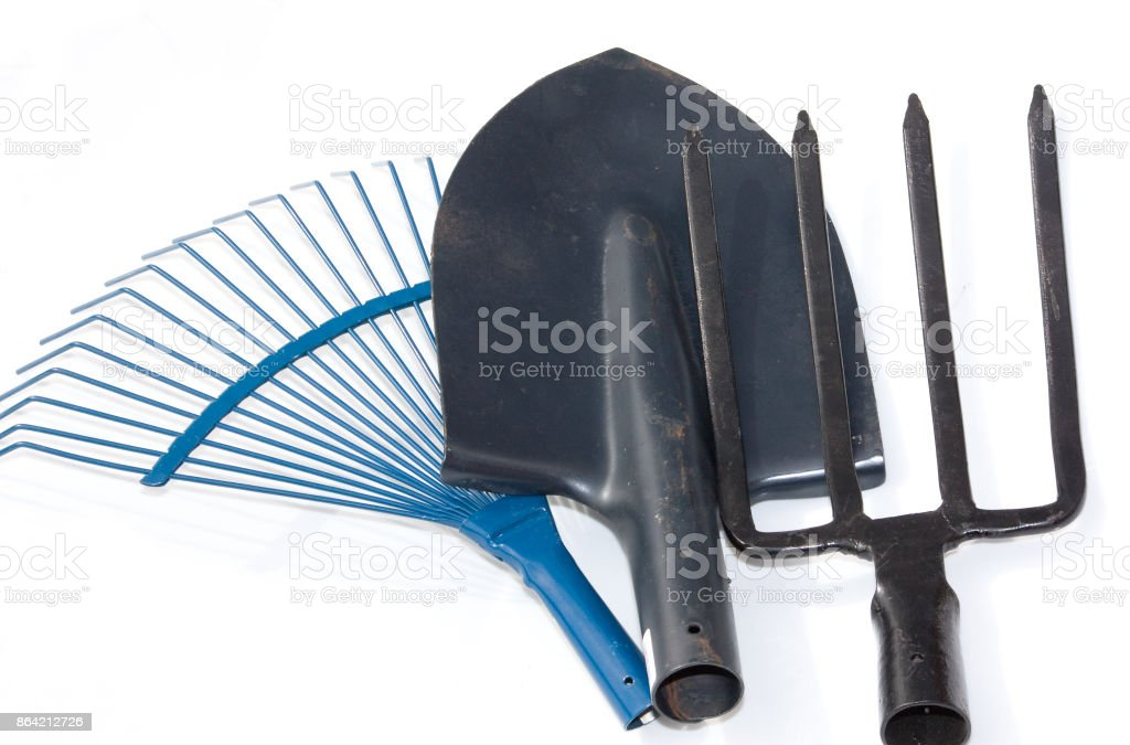 Gardening tools, spade, fork and rake isolated on white background royalty-free stock photo