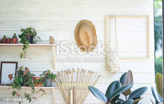 Gardening tools storage including straw hat, broomstick, succulent plants and flower pots.