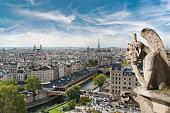 Gargoyle figur on Notre Dame looking towards Eiffel Tower at night