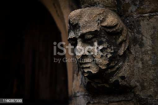 a stone gargoyle attached to a church doorway