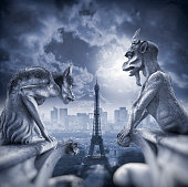 Gargoyle sitting on Notre Dame Cathedral and looking on Paris cityscape