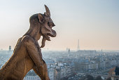 Frightening devilish gargoyle with horns and pig nose looks down
