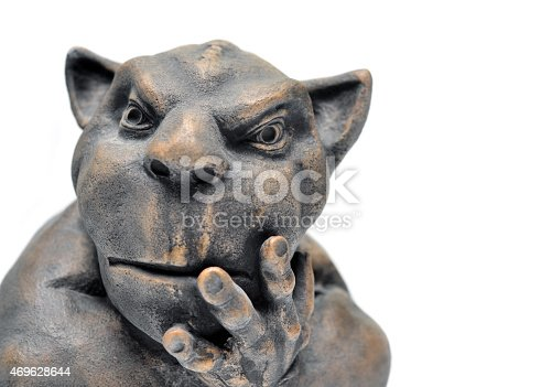 Closeup of a mass produced gargoyle statue on a white background with copy space,