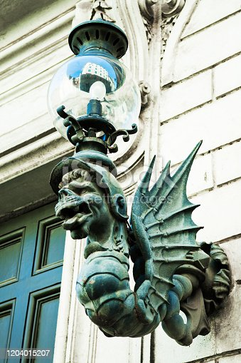 medieval gargoyle sconce light on a building in Rome, Italy.