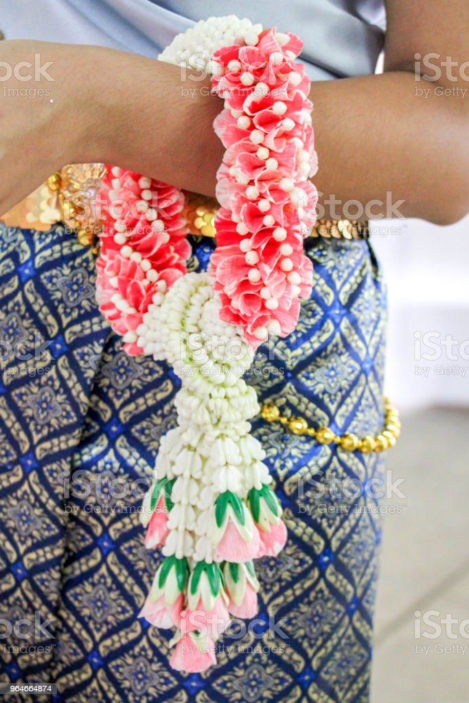 garland on Thai woman hand in traditional culture suit royalty-free stock photo