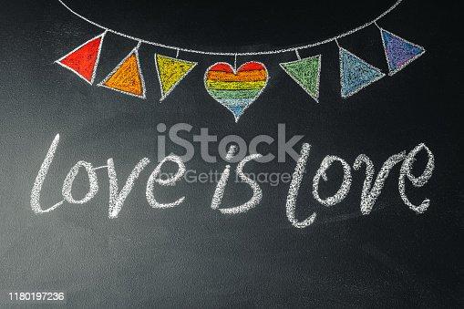 882318110 istock photo Garland with LGBT symbols drawn on chalk board with inscription love ia love 1180197236