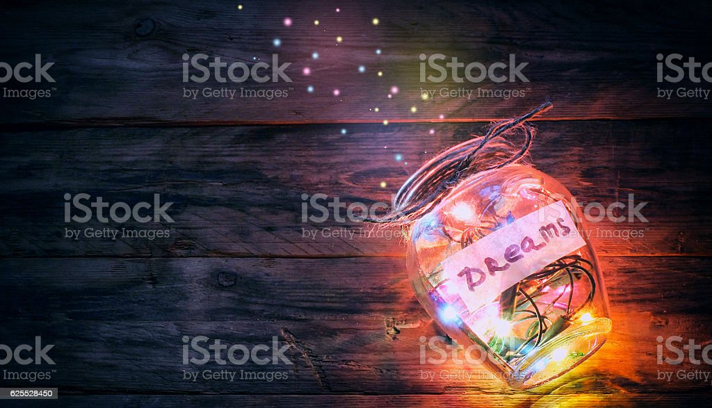 garlands of colored lights in glass jar with dreams stock photo