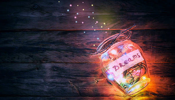 garlands of colored lights in glass jar with dreams - onirique photos et images de collection