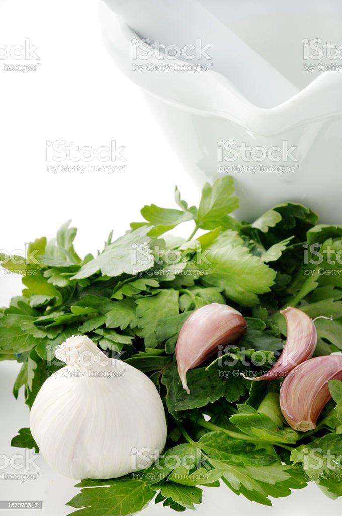 garlic and parsley next to mortar pesel royalty-free stock photo