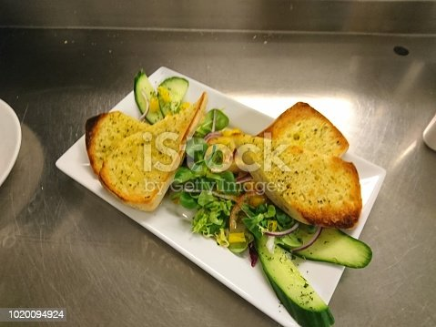 Photo of a garlic bread on a white plate garnished with fresh green salad