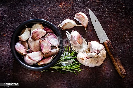 Vegetables: Garlic cloves in a black bowl shot from above on rustic brown background. A garlic bulb an three cloves are beside the bowl. An old kitchen knife is at the right of an horizontal frame. Predominant colors are brown and white. Low key DSRL studio photo taken with Canon EOS 5D Mk II and Canon EF 100mm f/2.8L Macro IS USM.