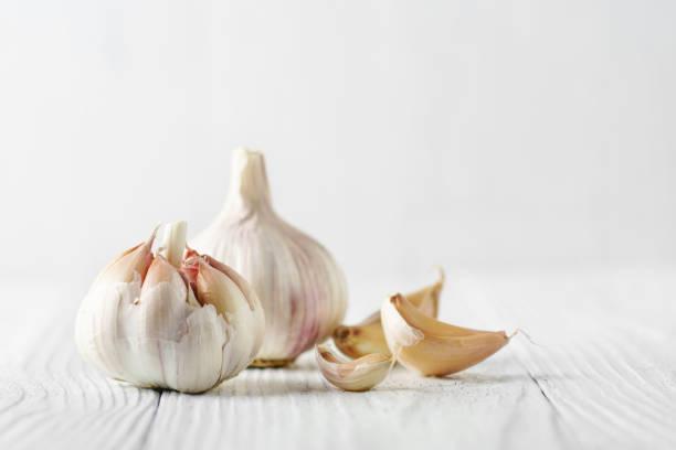 Knoblauchzwiebel mit Knoblauchzehen in weißem Holz. – Foto