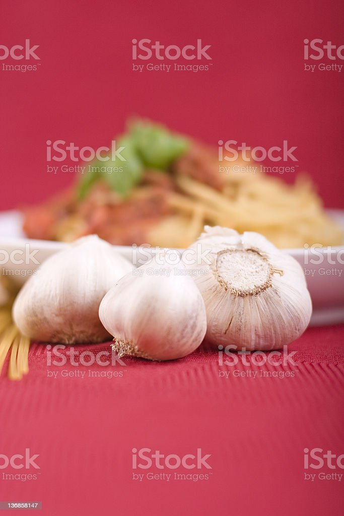 Garlic Bulbs & Pasta Three garlic bulbs rest in front of a large dish of pasta. Color Image Stock Photo