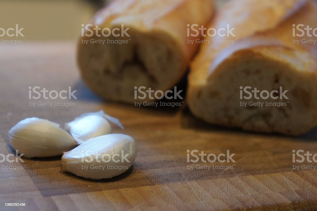 Garlic cloves and a cut loaf baguette on a counter stock photo