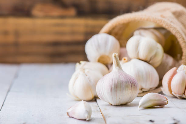 garlic cloves and bulb for food cooking in the kitchen - garlic stock photos and pictures