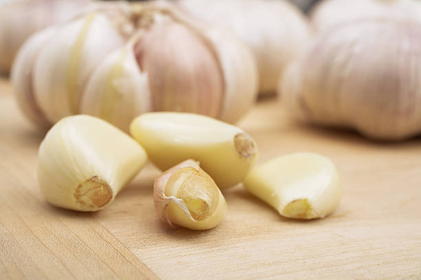 Garlic cloves on a wooden board stock photo
