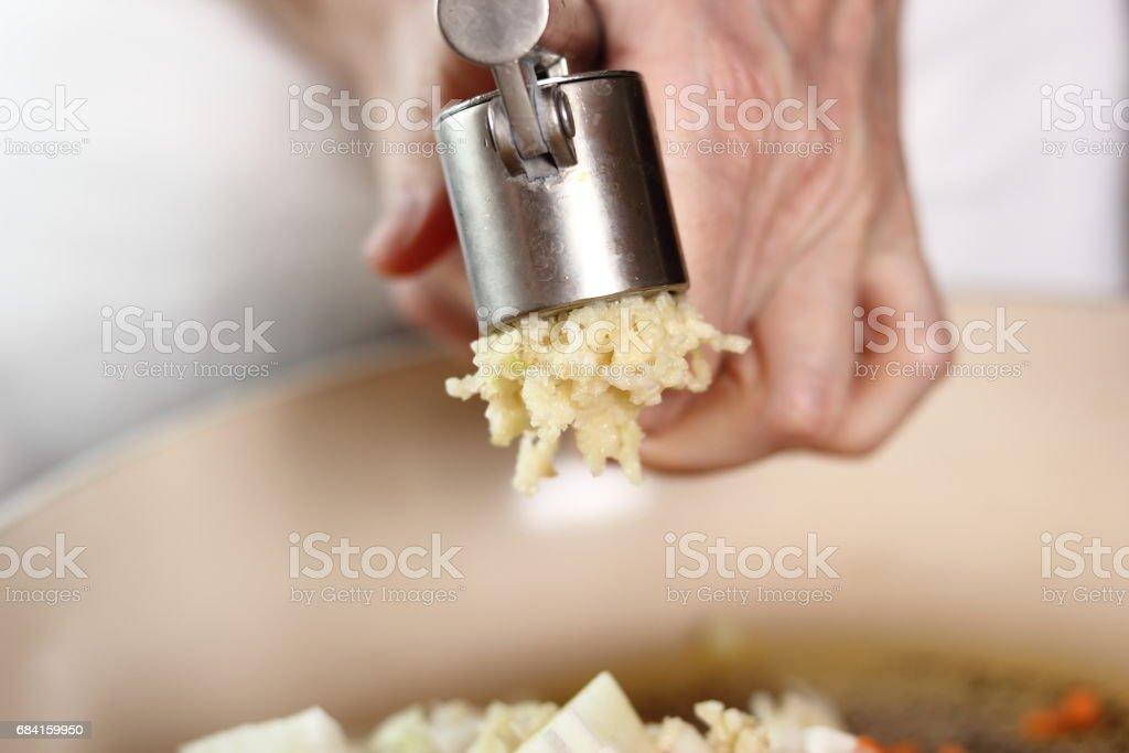 Garlic crushed using a garlic press. Making Lasagna Bolognese Series. royalty-free stock photo