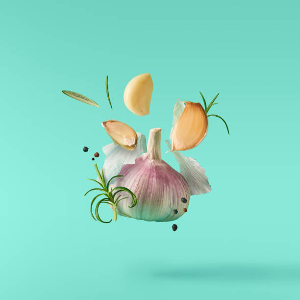 garlic falling in air with pepper and herbs like rosemary on turquoise background. - garlic stock photos and pictures