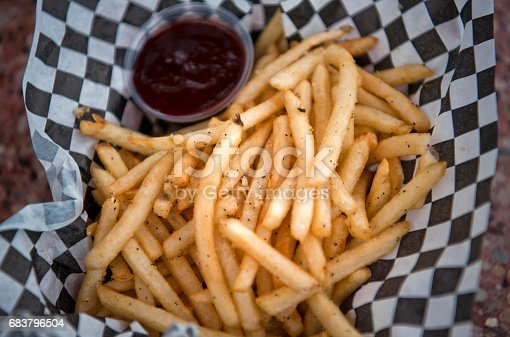 Rosemary garlic fries sit in a basket with barbecue sauce.