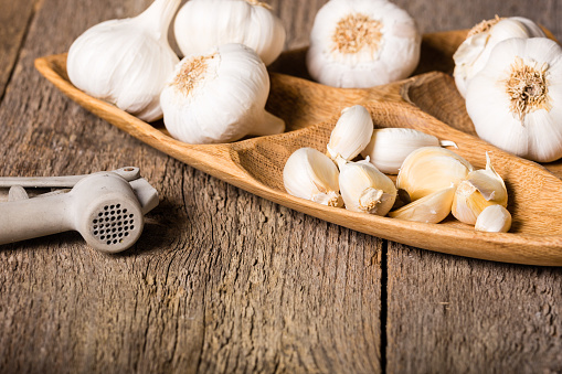 Garlic, Garlic cloves and Garlic bulb in vintage handmade wooden bowl.