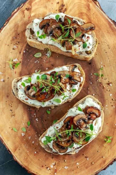 knoblauch champignons toast mit cremigen herbed ricotta käse verteilen - pilzpfanne stock-fotos und bilder