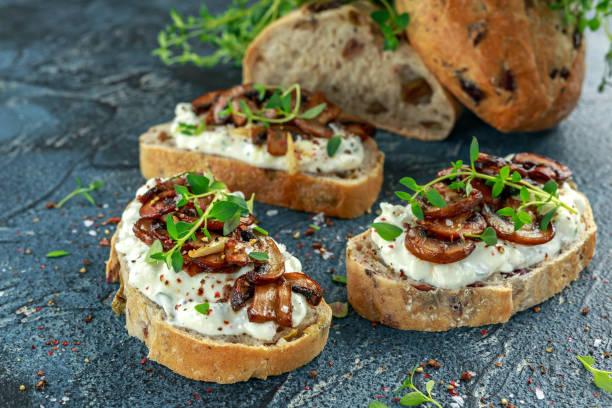 Garlic mushroom toast with creamy herbed ricotta chees spread - foto stock