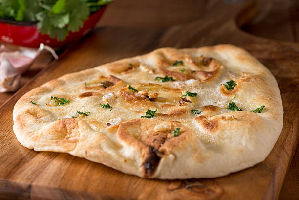 Garlic Naan Bread A delicious homemade garlic naan flatbread with garlic butter and cilantro. naan bread stock pictures, royalty-free photos & images