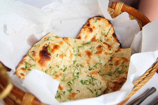 Garlic Naan Indian Flatbread Two pieces of garlic naan bread in a basket. naan bread stock pictures, royalty-free photos & images