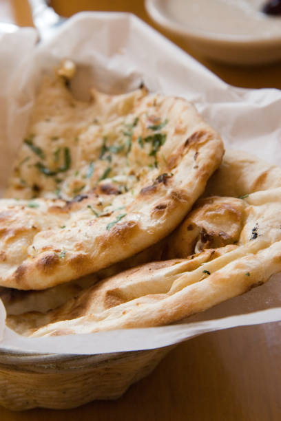 Garlic naan Indian flatbread pieces Two pieces of garlic naan bread in a basket. naan bread stock pictures, royalty-free photos & images