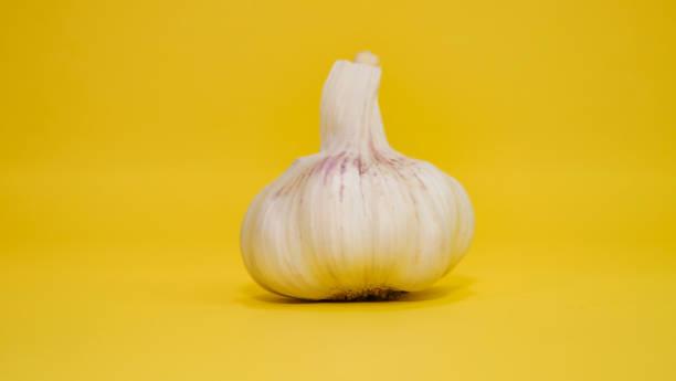 Garlic on a yellow background stock photo