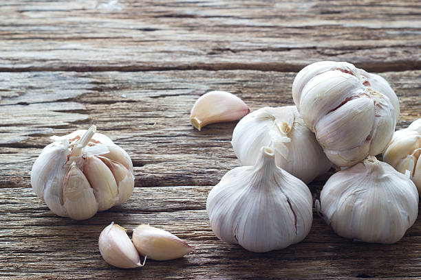 garlic on the wooden background - garlic stock photos and pictures