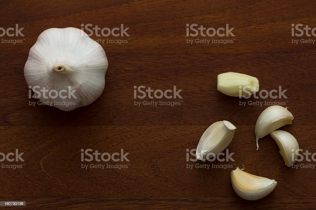 Garlic on wooden kitchen board viewed from directly above stock photo