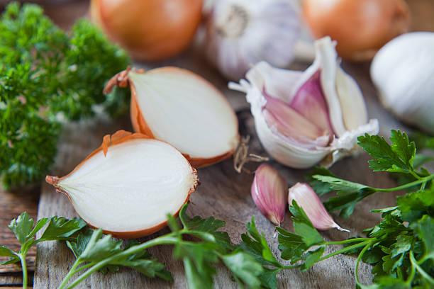 garlic, onion and shallots on wooden board. - sjalot stockfoto's en -beelden