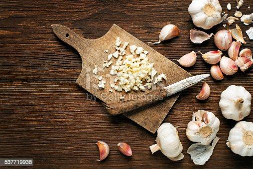 Garlic cloves and sliced garlic on vintage wooden background.