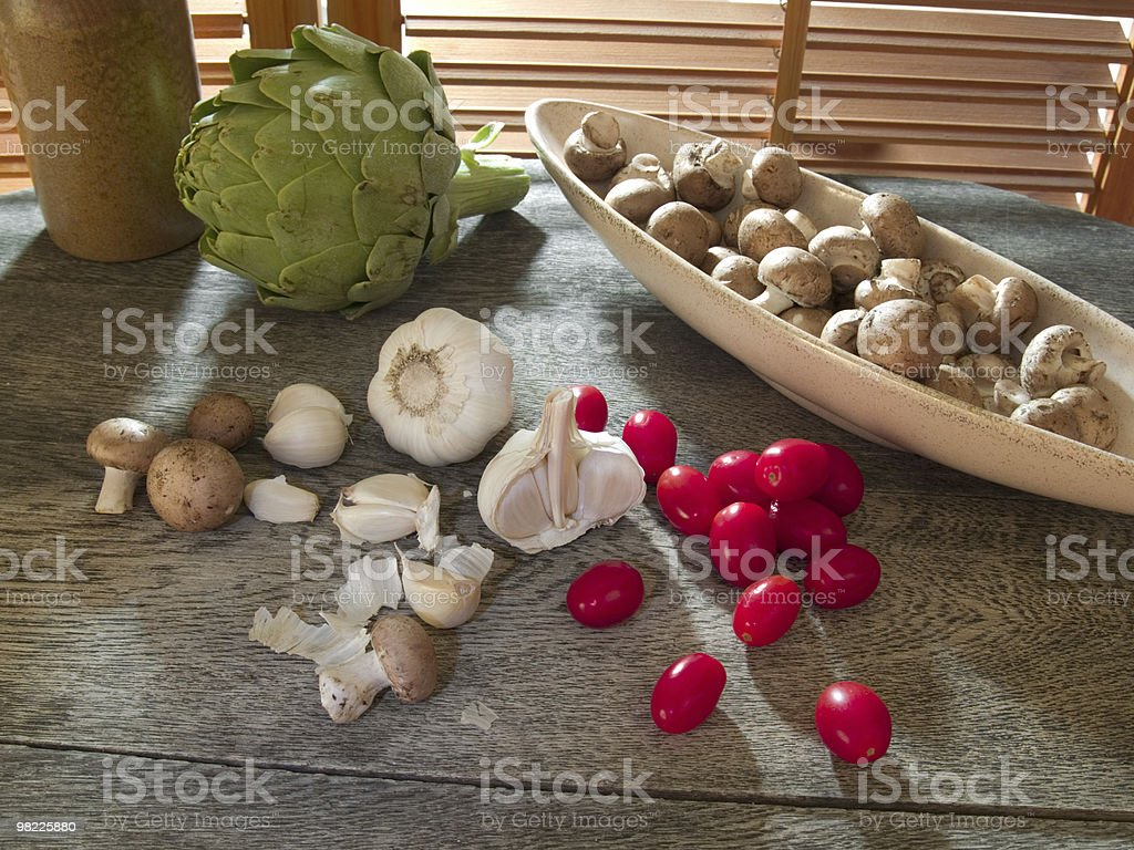 Garlic with cherry tomatoes, crimini mushrooms and an artichoke royalty-free stock photo