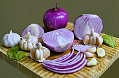 A beautiful presentation of garlic and red onions in a close-up capture showing cloves of garlic to bulbs to sliced onions in a range of variations
