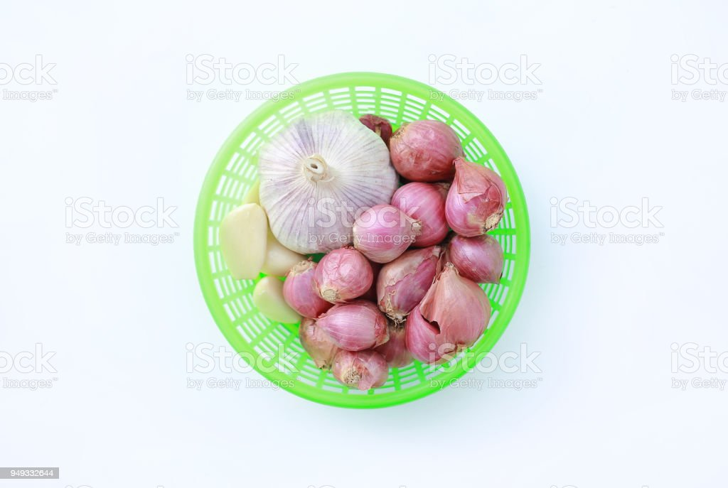 Garlics and onion in green basket isolated on white background. Top view. stock photo