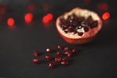 ripe beautiful cut pomegranate on a black background with red lanterns. pomegranate seeds are scattered nearby.