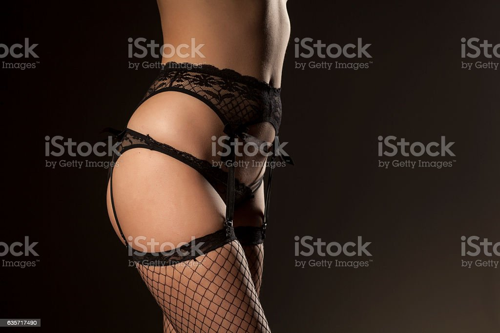 garter, sexy panties and fishnet stockings on dark background stock photo