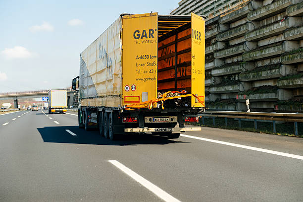 Gartner Speditions truck on highway Stuttgart, Germany - March 26, 2016: POV point of view of a driver looking at Mercedes-Benz cargo truck with Gartner Speditions logotype transporting steel tubes driving on bundesautobahn or Federal Motorway highway street signs to Mannheim, Karlsruhe, Rastatt-Nord, Baden-Baden and Sandweier singen stock pictures, royalty-free photos & images