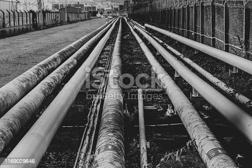 Gas and oil pipelines stretching between a port (the Port of Belfast) and a fuel storage facility.  Image taken from public footpath, through a chain link fence.  Belfast, Northern Ireland.  Black and white.