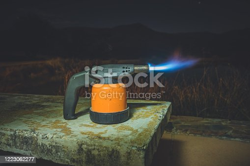 Gas blow torch on fire with long blue flame. It is standing on concrete bench at night time.