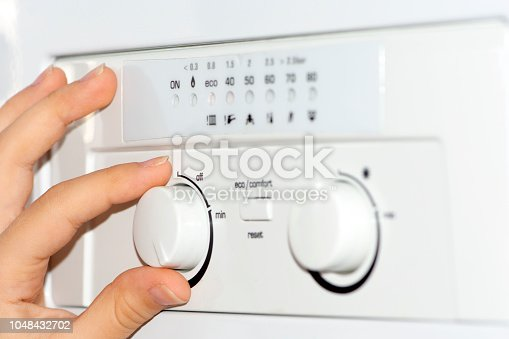 istock gas boiler and woman hand 1048432702