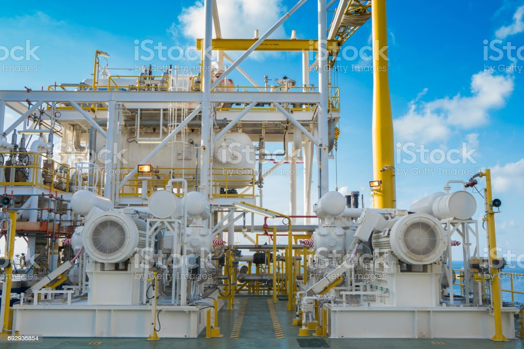 Gas booster compressor in vapor recovery unit and behind is reflux drum these system for recovery heavy hydrocarbon lost in light end gases at oil and gas central processing platform stock photo