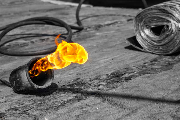 gas burner with fire and roll of roofing material on blurred background with bokeh effect gas burner with fire and roll of roofing material on blurred background with bokeh effect major military rank stock pictures, royalty-free photos & images