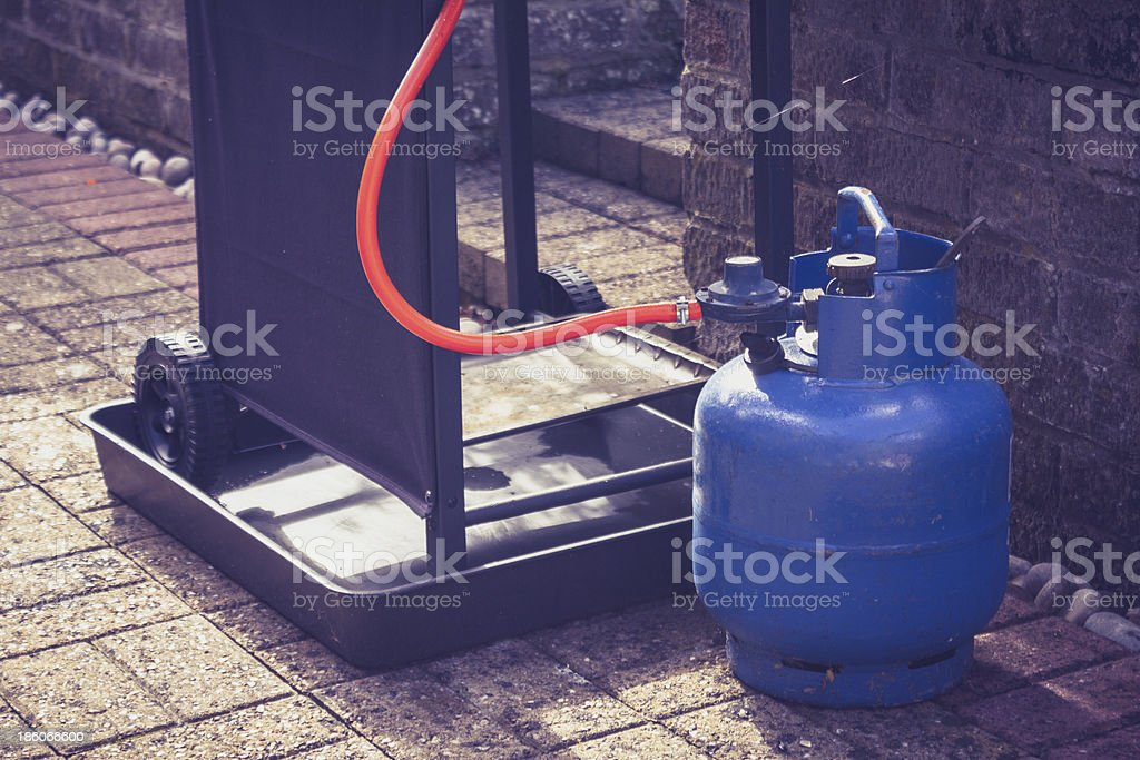 Gas canister and portable barbecue Large blue gas canister attatched to a portable barbecue on wheels in a domestic garden American Culture Stock Photo