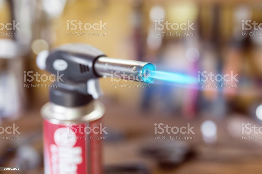 Gas cartridge gun lighter .Close-up nozzle of burner with blue flame jet. Workshop background, scorching of wood stock photo